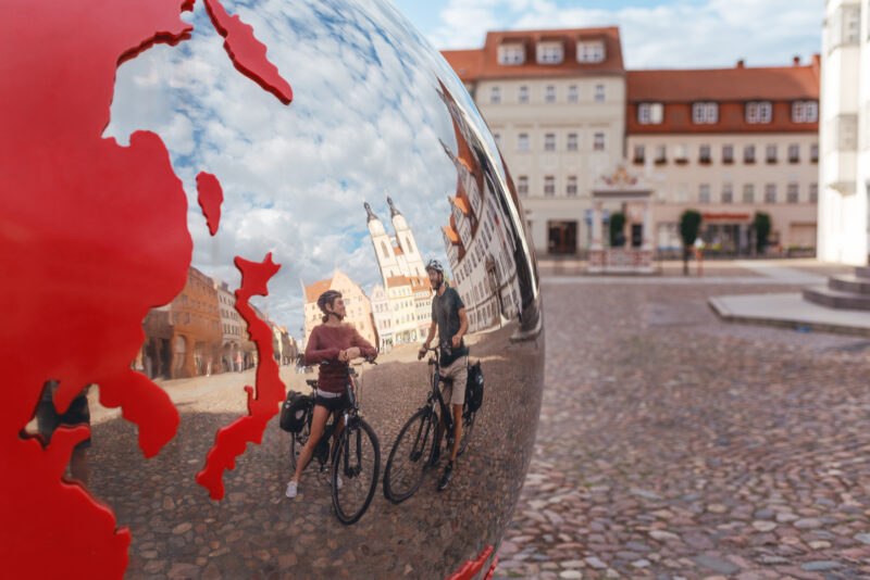 Radfahrer vor der Weltkugel in Wittenberg