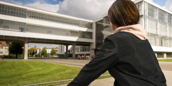 Radfahrerin vor dem Bauhausgebäude Dessau